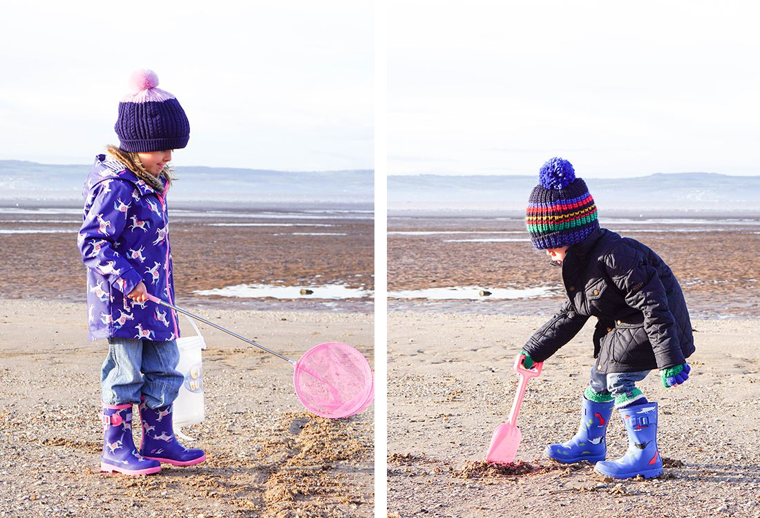 children wearing printed kids wellies and rainwear with bobble hats on beach