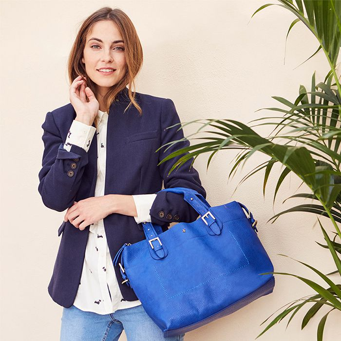 woman wearing navy blazer with leather tote bag