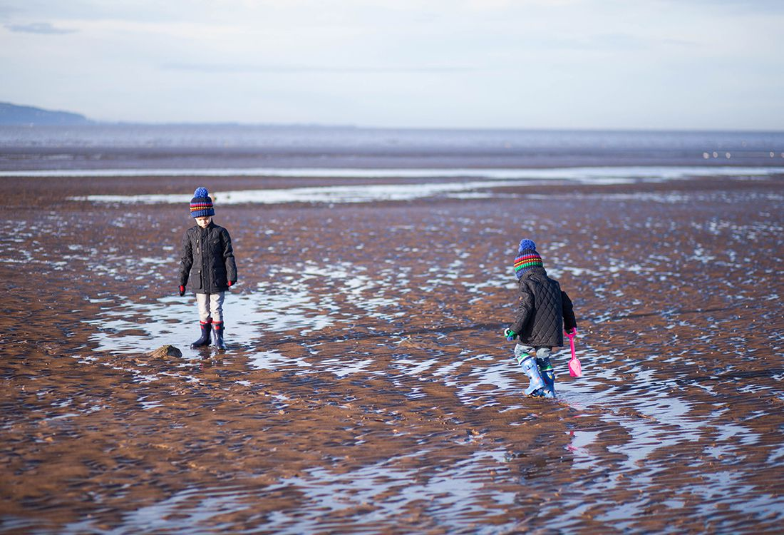children exploring beach in joules outerwear
