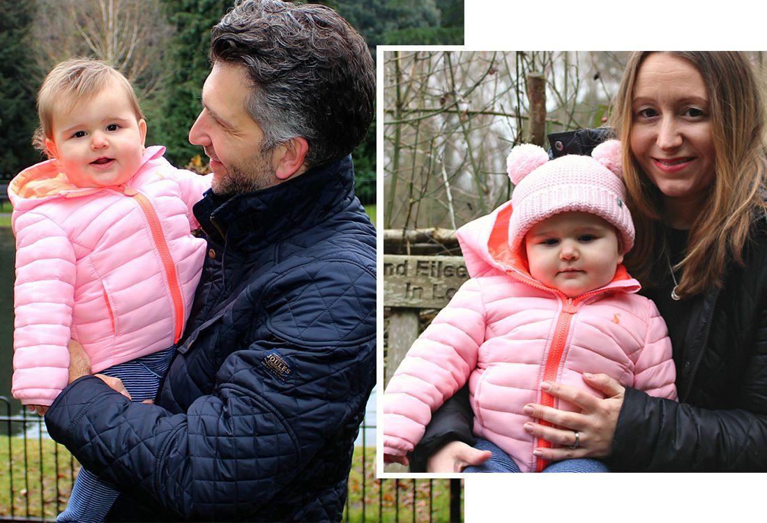 baby wears pink padded waterproof coat whilst be held by father