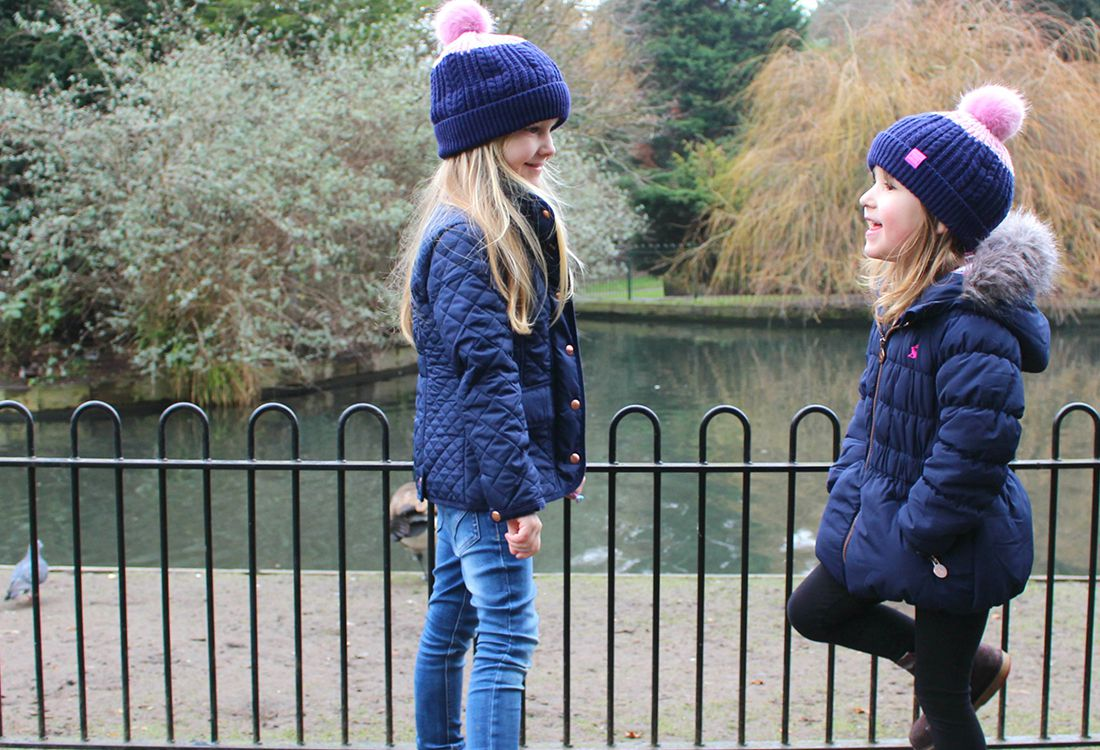 girls model joules waterproof navy coats and bobble hats in park