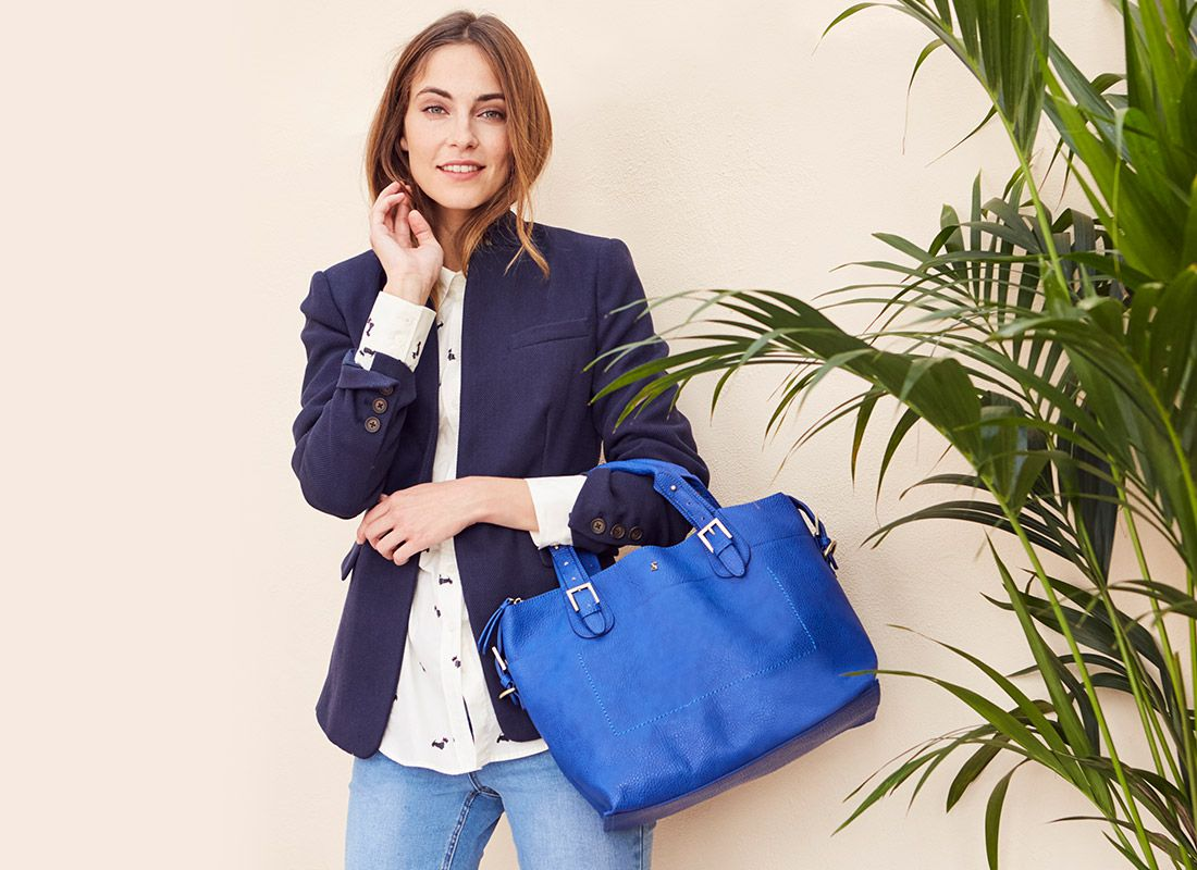 woman modelling navy tailored blazer with leather tote bag