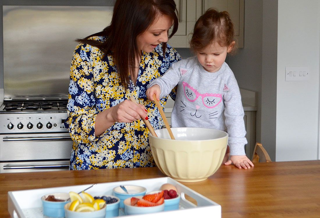 mother and daughter cook pancakes for pancake day in joules clothing