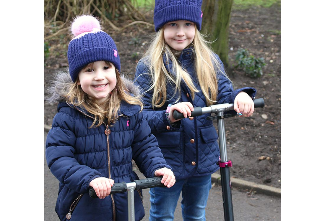 girls wearing bobble hats and waterproof quilted coats play on scooters