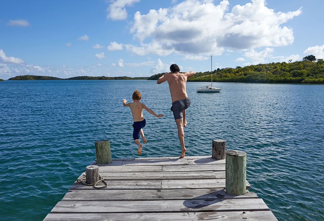 father and son jumping into the sea for father's day