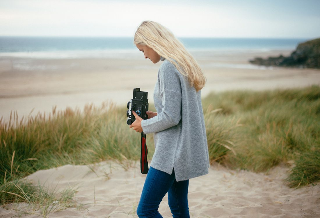 cornish coastal scene with female model taking photos on the beach