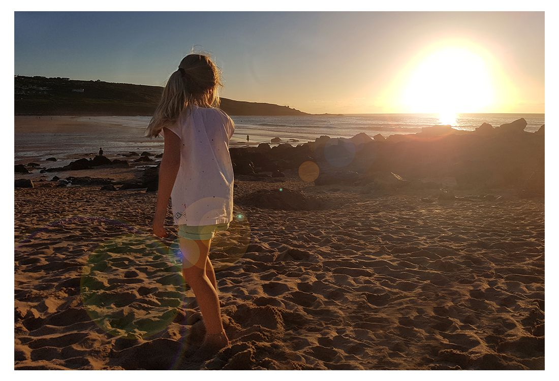girl playing in the sand with the sun set in the background