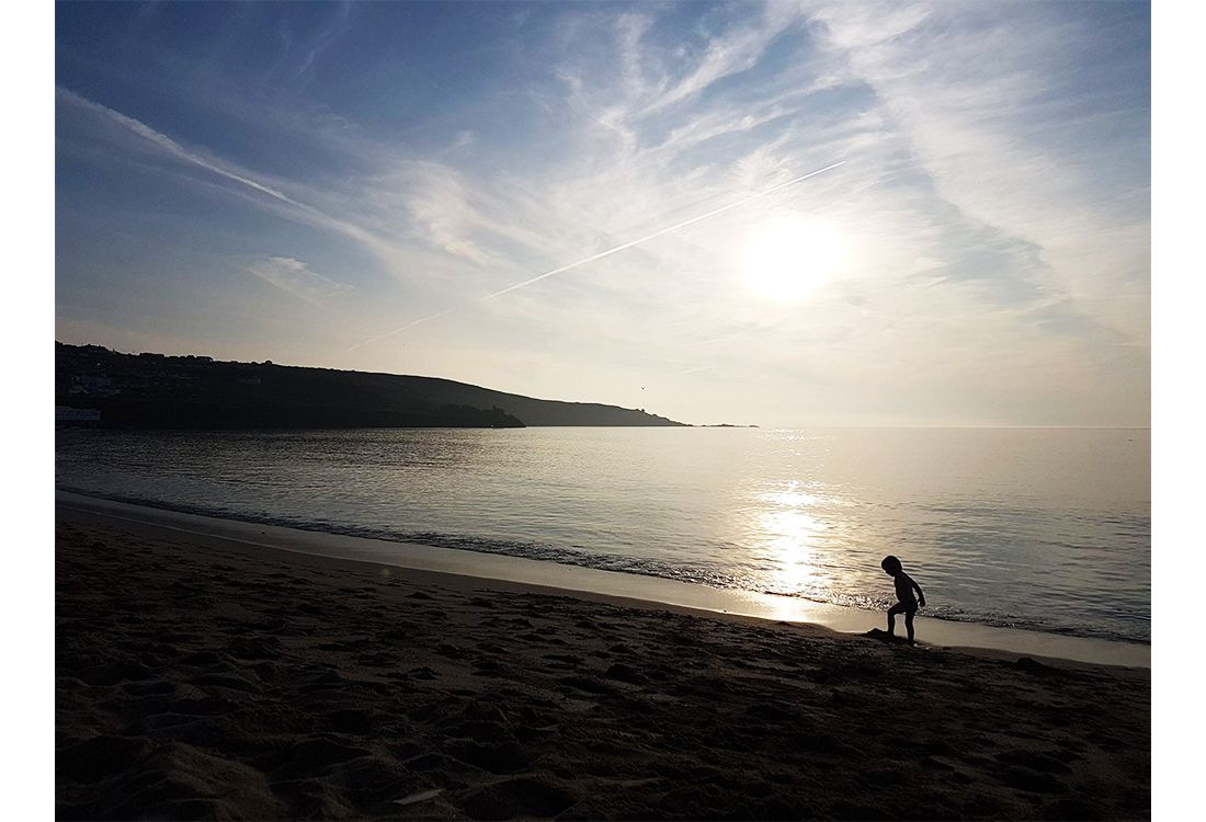 the sun set on the beach in st ives