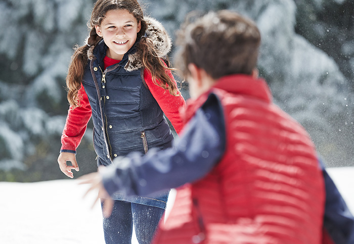 Children playing in the snow wearing Joules gilets