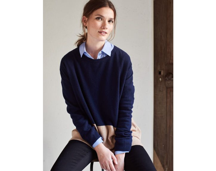 Woman sitting on a stool wearing a Joules knitwear jumper