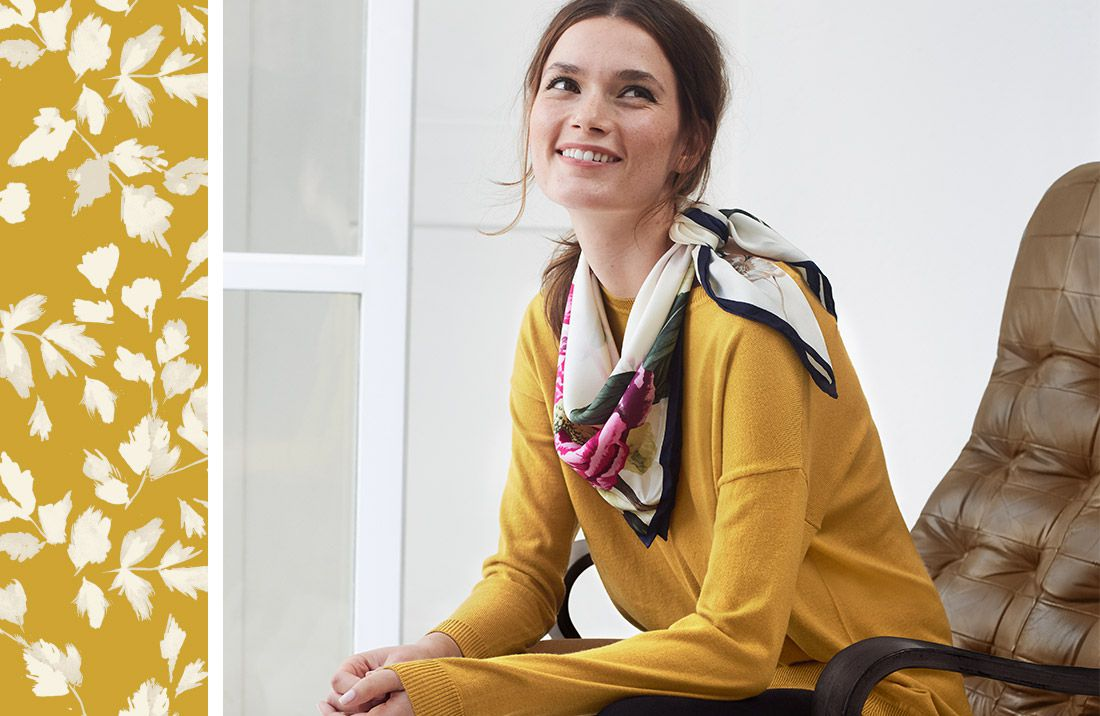 Woman wearing Joules jumper and scarf with floral print border