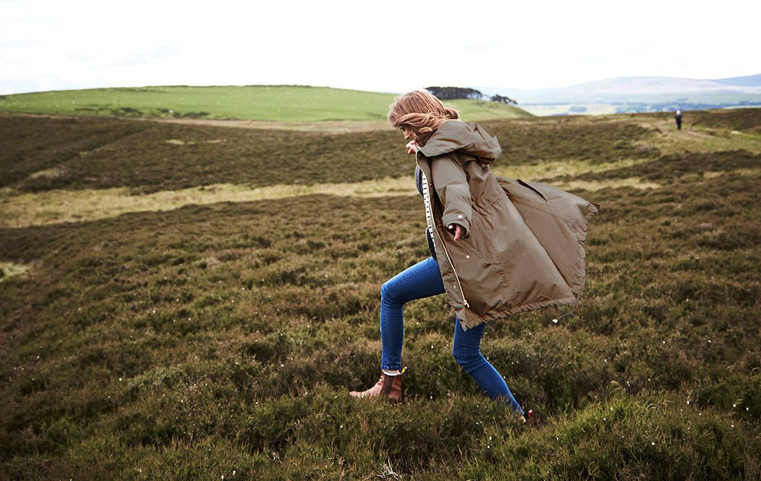 woman in a raincoat running through the countryside