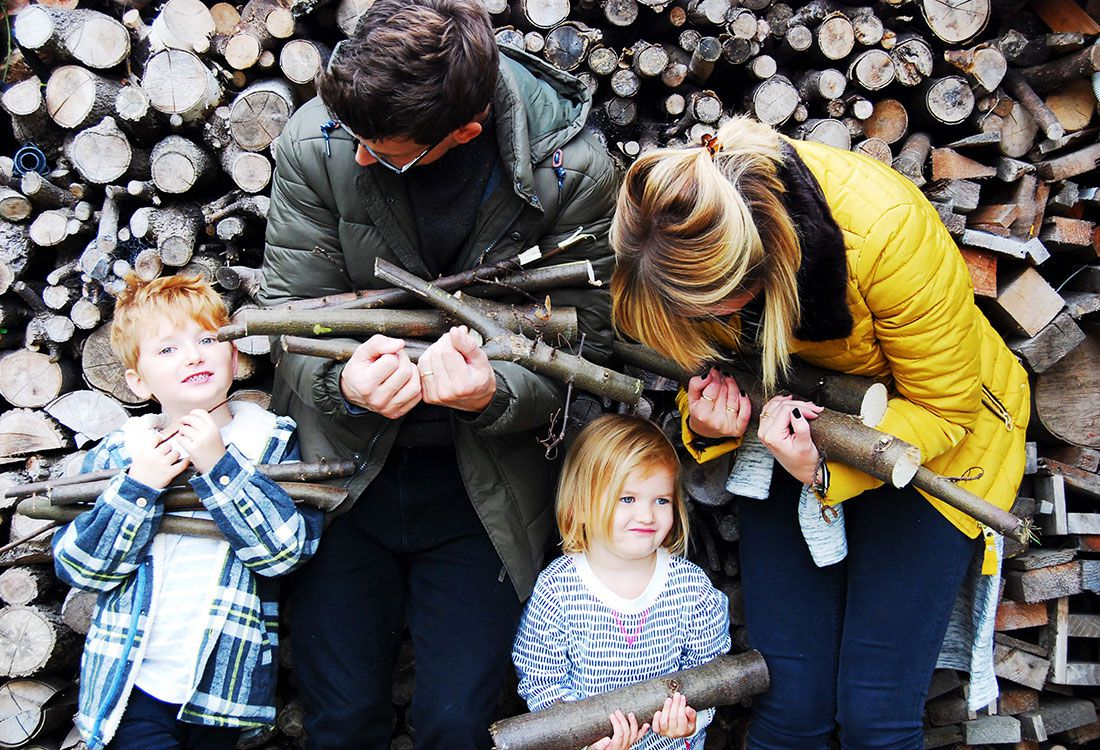 family pose in front of log wall whilst holding a selection of sticks