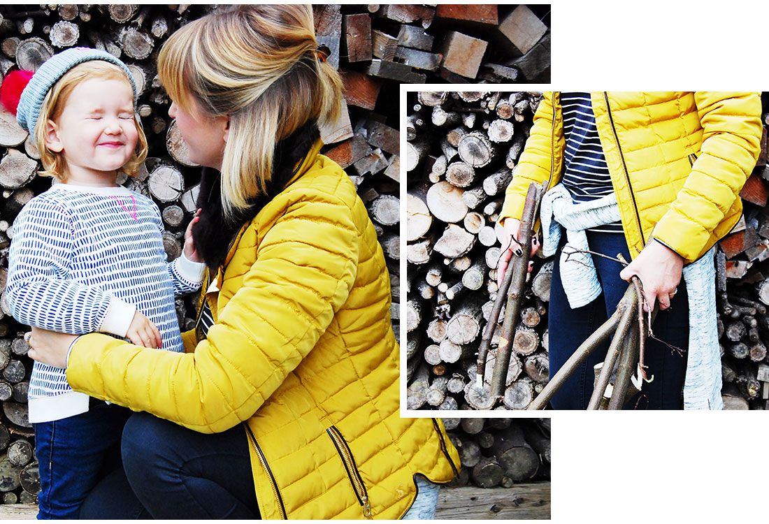woman playing with girl in front of wall of logs