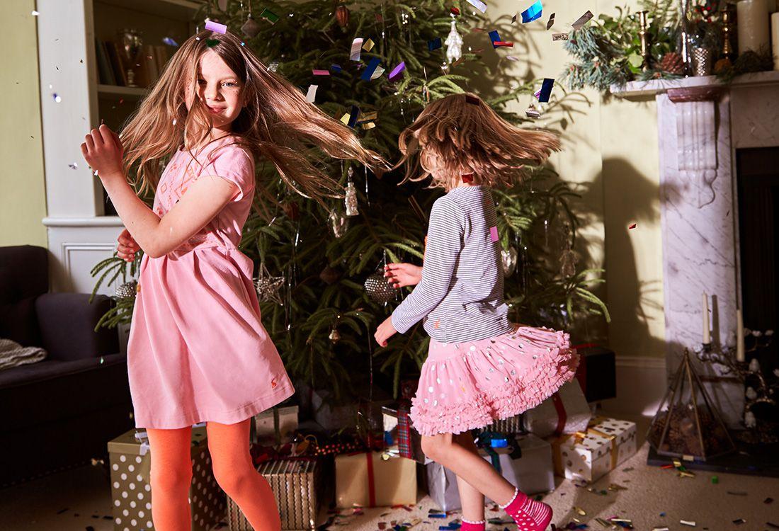 girls dancing around a christmas tree