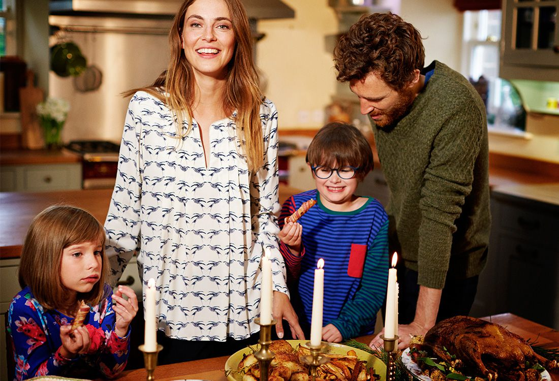 family standing round a festive christmas table