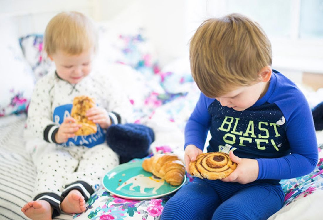 boys enjoying breakfast pastries in fun printed nightwear