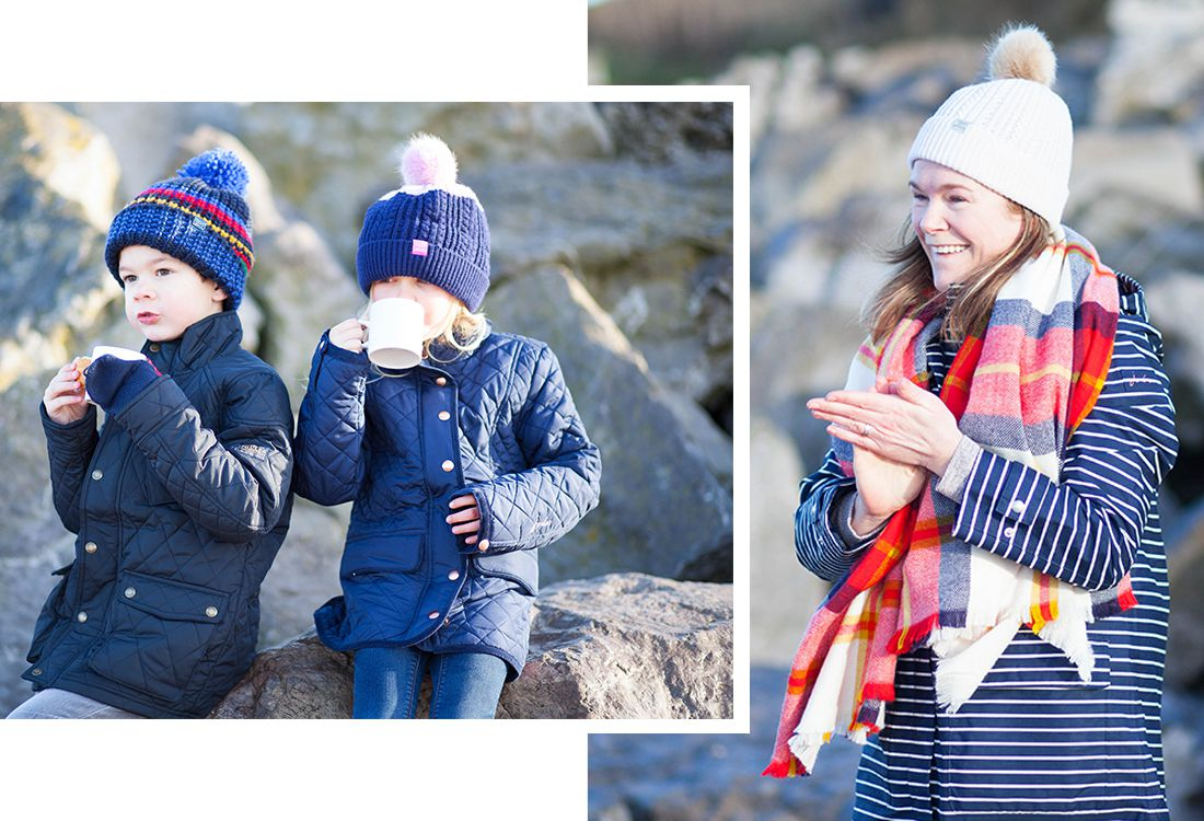 family wearing joules warm welcome collection with bobble hats and coats drinking and eating picnic