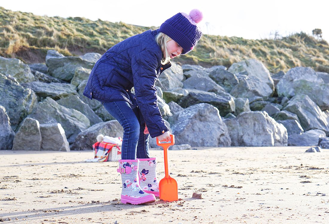 joules wellies and bobble hat worn on a child on beach