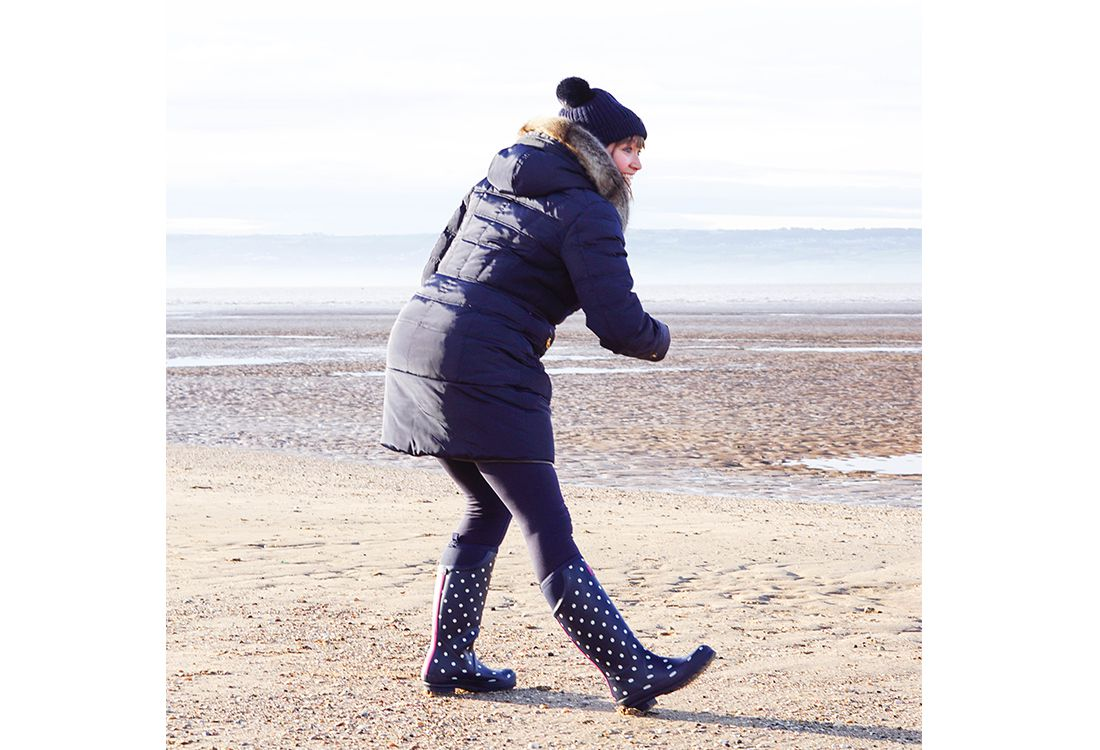 women in navy padded coat and spotted wellies playing frisbee on beach