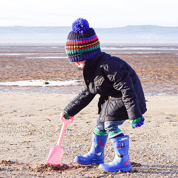 boy wears printed wellies and quilted jacket with bobble hat on the beach