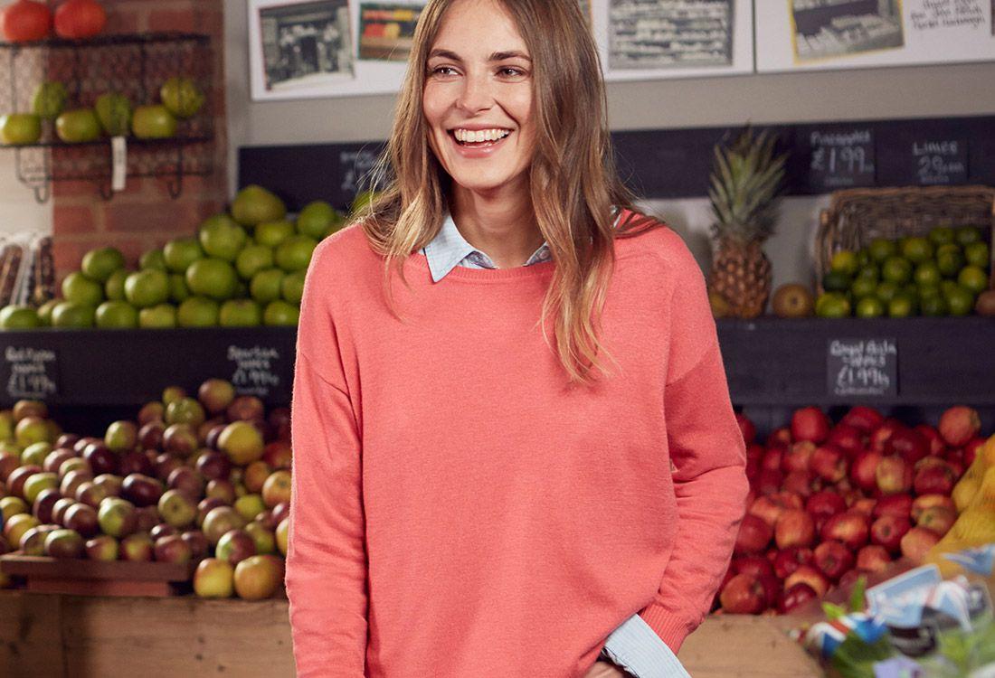 female modelng peach jumper in fruit and veg market