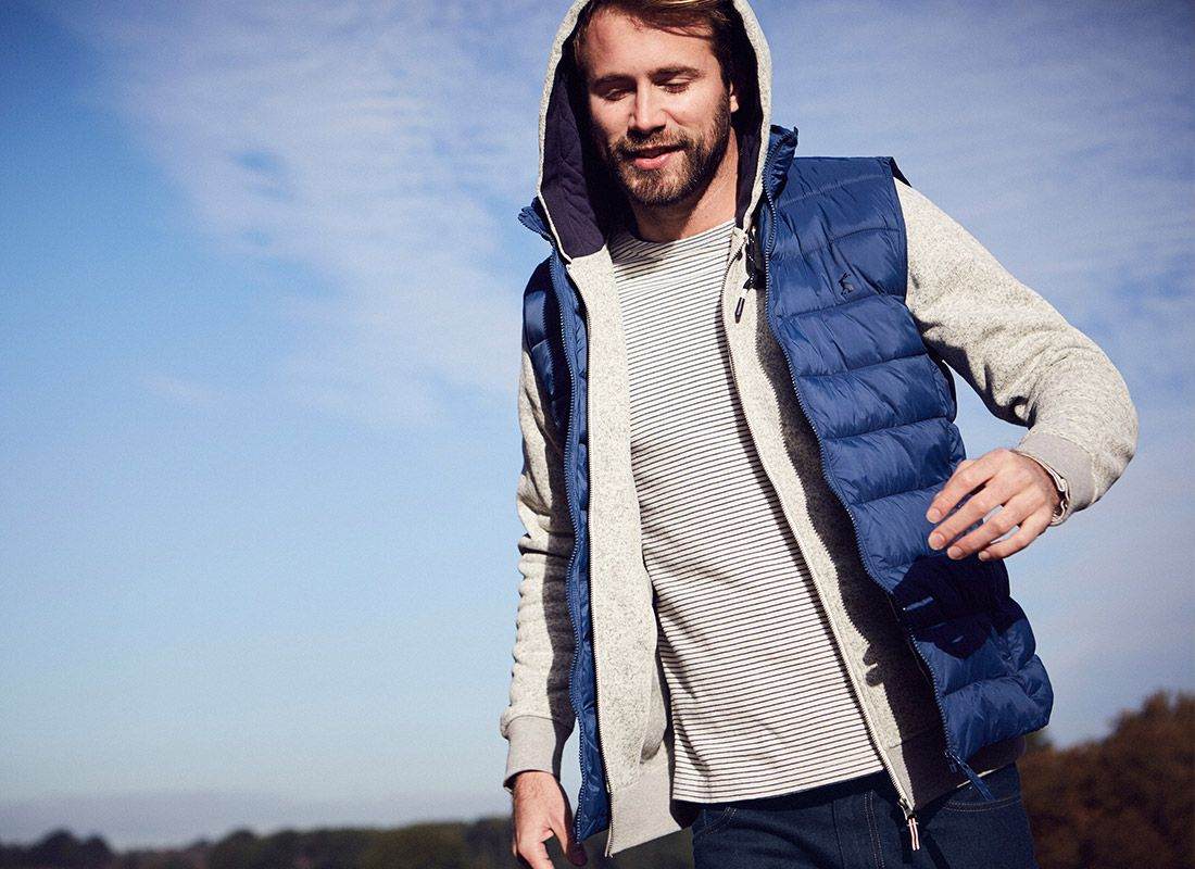 man models blue gilet with blue sky background