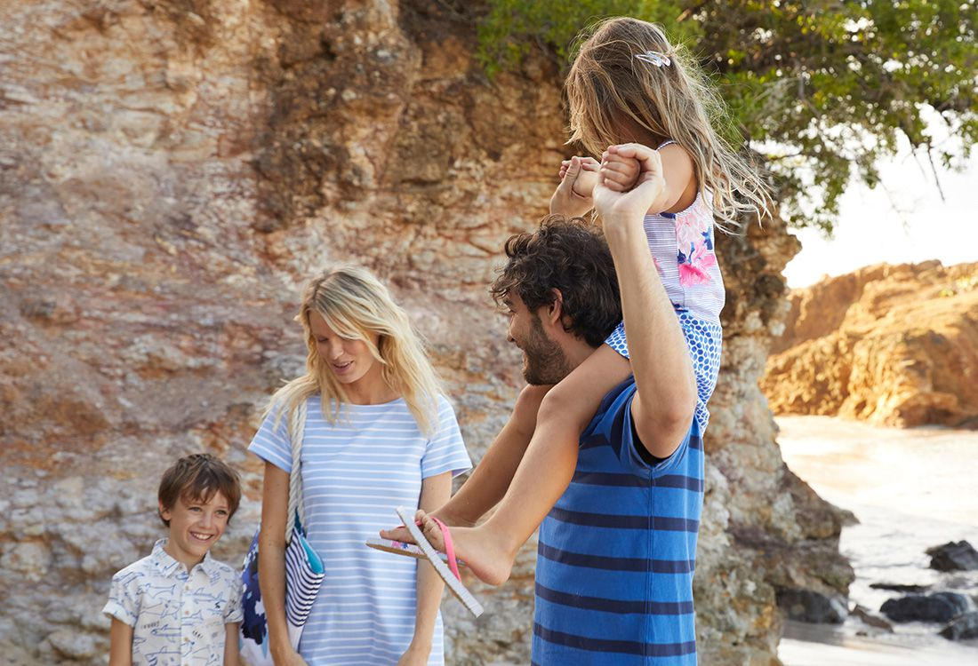 Family walk along beach on summer holiday in their summer staples