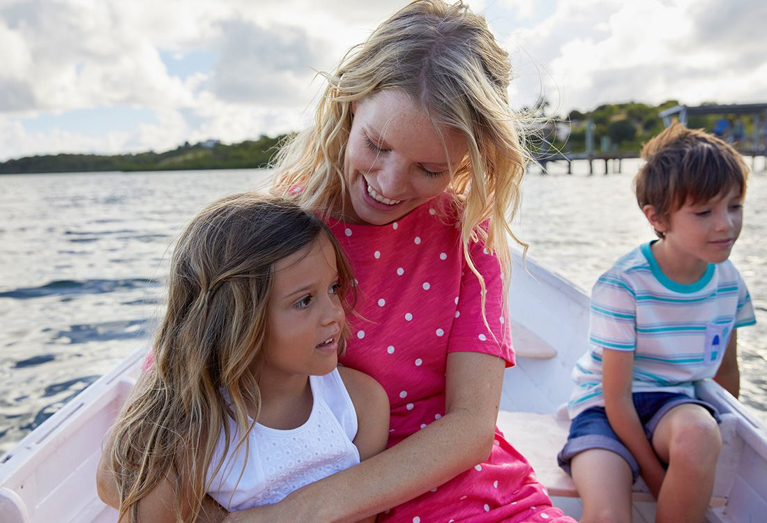 mother and children relax on boat in summery scene