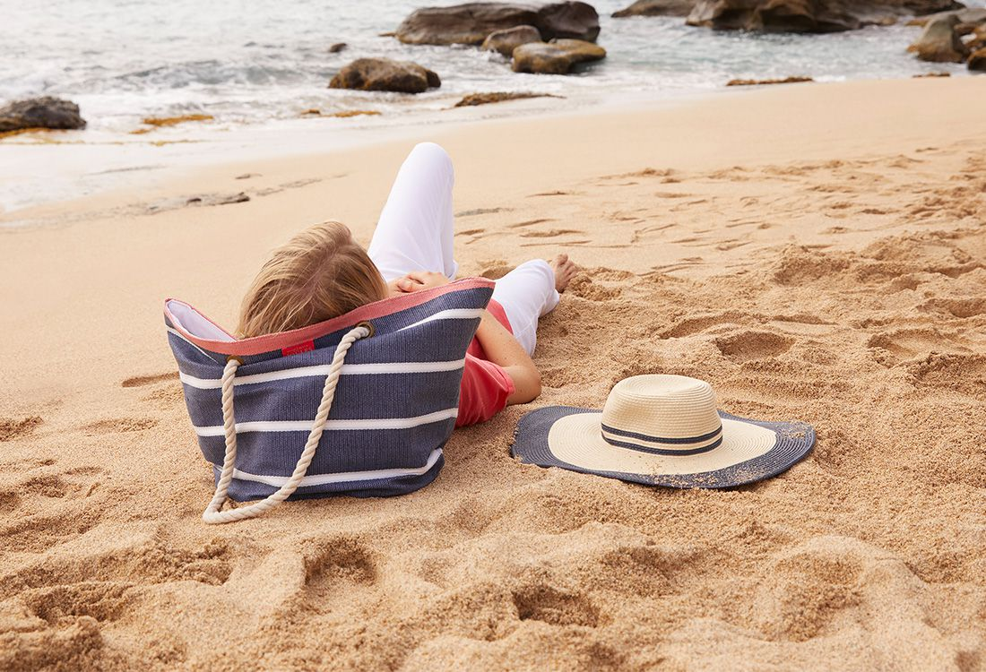 lady relaxes on sandy beach with her summer holiday accessories