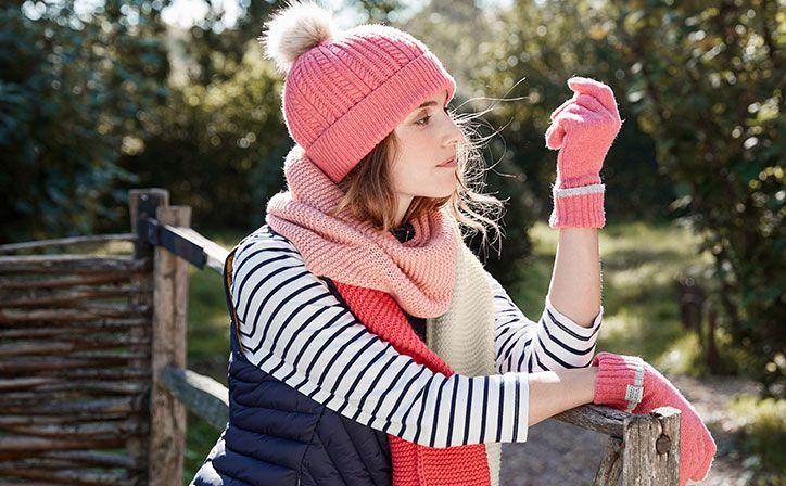 woman wears winter bobble hat and scarf in garden