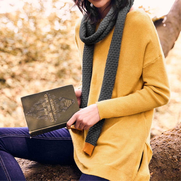 Woman wearing a knitted jumper and scarf reading a book